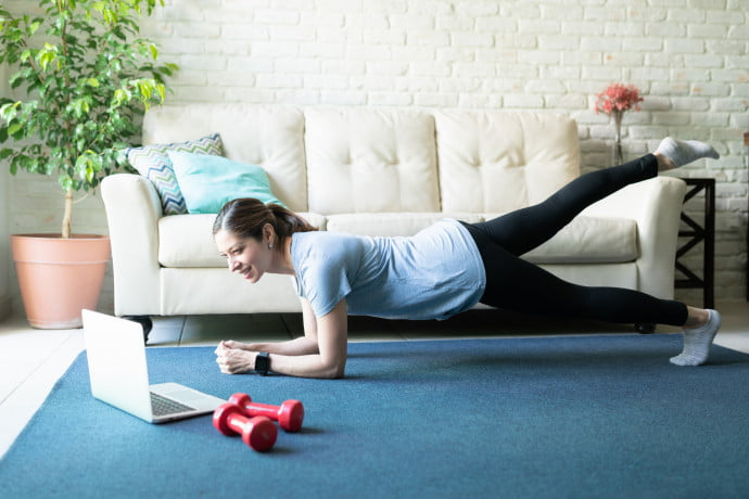 lady doing Pilates in her living room looking at the laptop