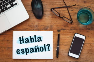 Learn spanish sign on desk with laptop and phone for online lesson