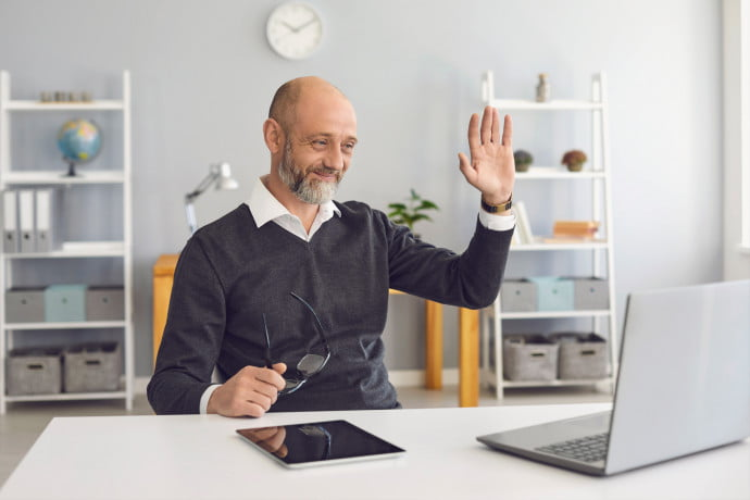 Man-waving-to-fellow-learners-in-front-of-laptop-in-his-living-room