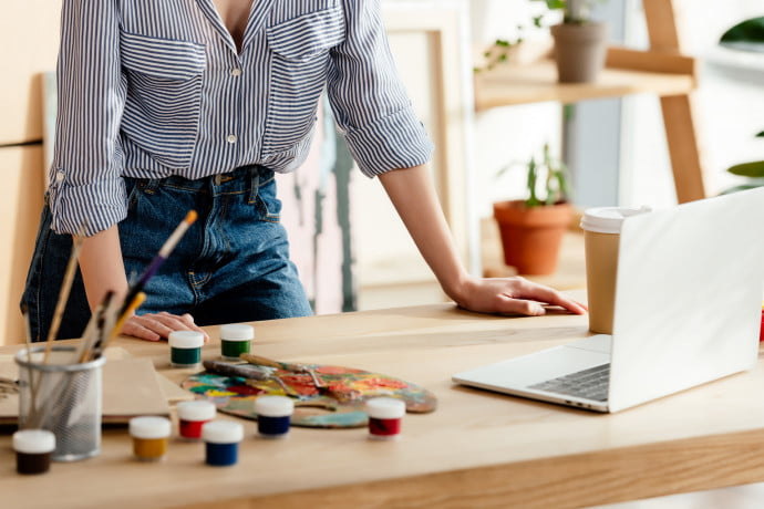 Woman standing in front of laptop ready to join online Painting Classes