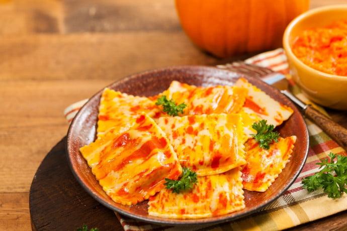 Pumpkin raviolli on a plate with tomato ragu