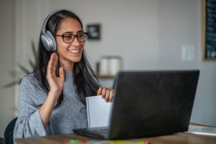 Woman leanring spanish in front of the computer with headphones on