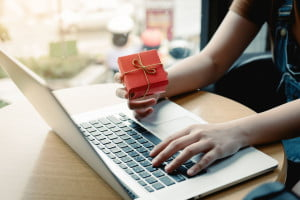 Woman in front of computer with gift box