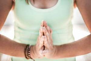 Image of woman with hands in prayer for Yoga nameste