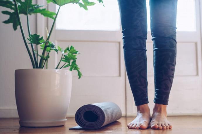 Introductio to pilates image of woman standing next to pilates mat