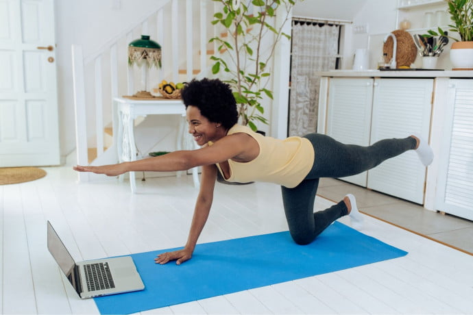 Lady doing pilates in her living room pushing her practice