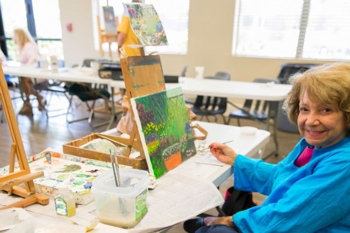 Woman painting with easel and canvas on table